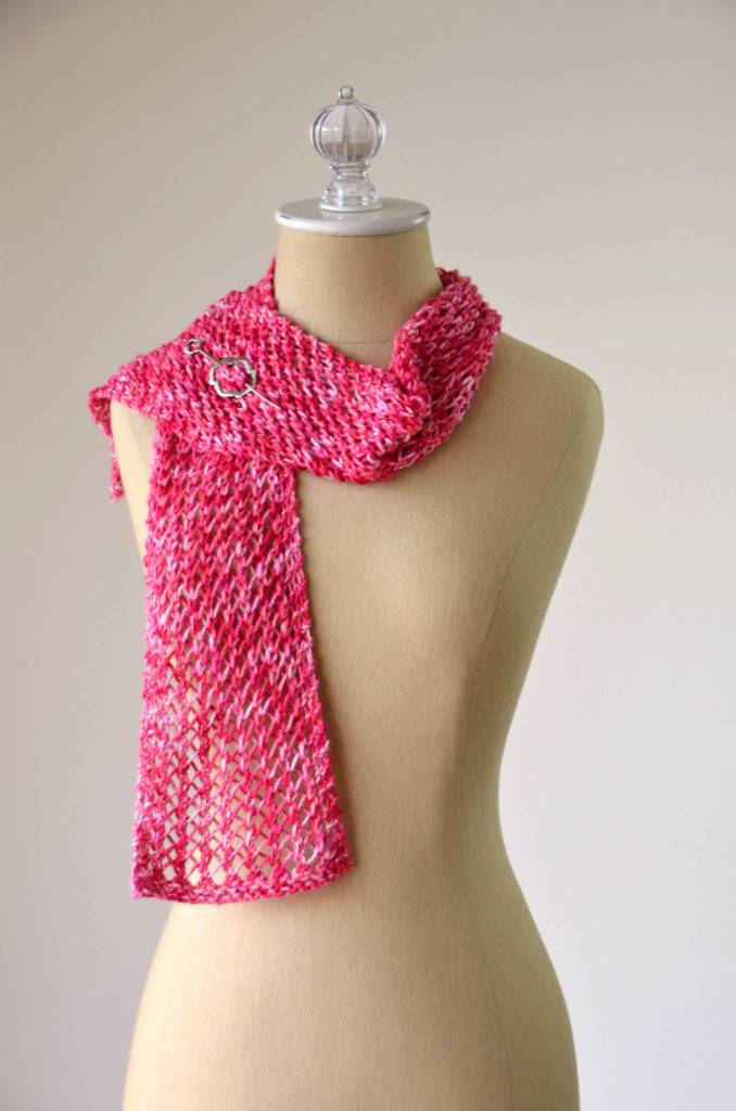 A red lace scarf with one end thrown over the shoulder of a dressform. A silver shawl pin fastens the scarf together.