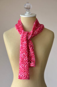 red lace cotton scarf tied at the neck on a dressform