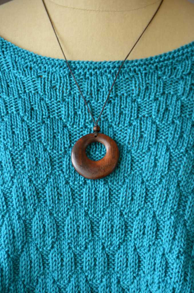 closeup of aqua knitted poncho with wooden necklace
