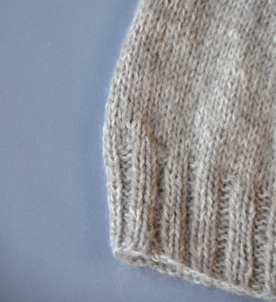 Closeup image of the ribbed brim and body of a knitted hat