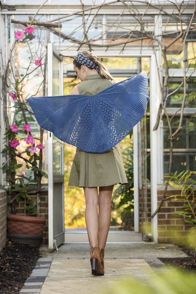 Woman facing away from camera showing blue shawl knit in Cottonwood