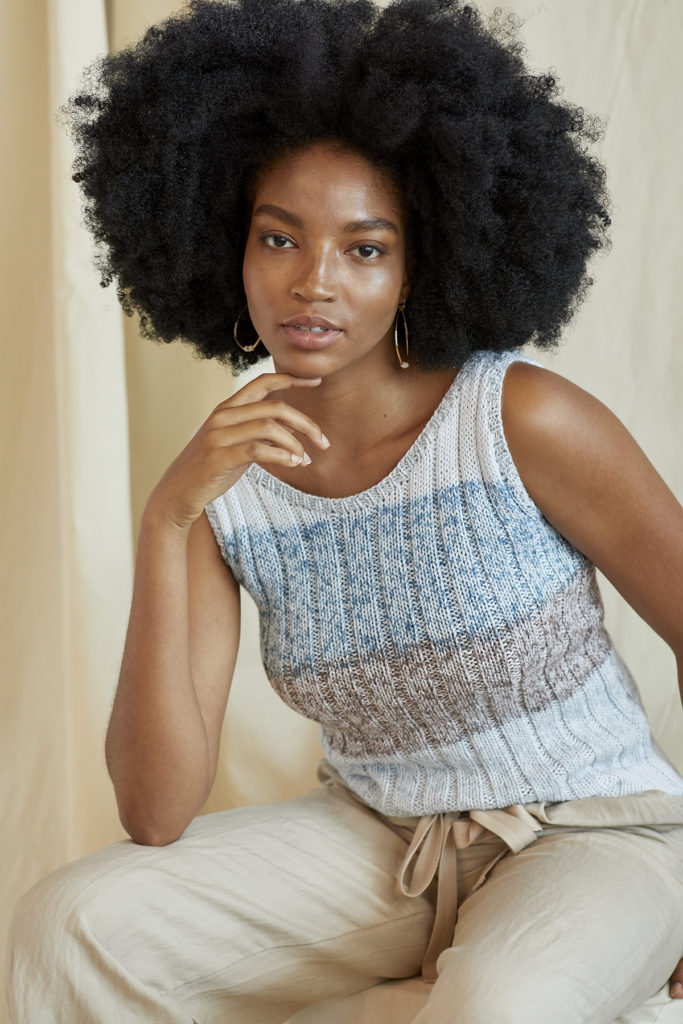 Seated woman wearing ribbed knitted cotton tank top