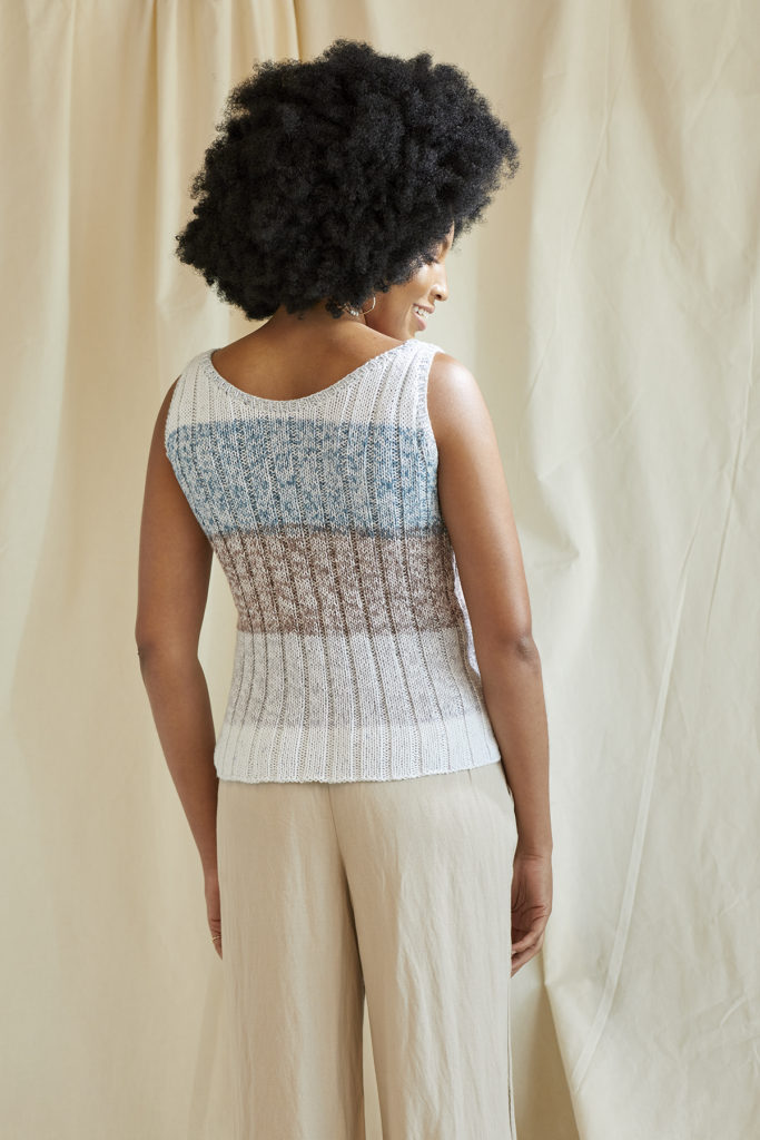 Rear view of woman wearing blue, grey, and taupe tank top